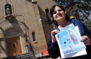 Artist Carlota EspinoZa holds a photo of her work in April in front of Our Lady of Guadalupe Church in Denver. Church parishioners have started a grassroots effort to protest a wall that has replaced EspinoZa's long-standing mural in the building.